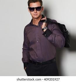 stylish man with a handbag. Handsome man in sunglasses
