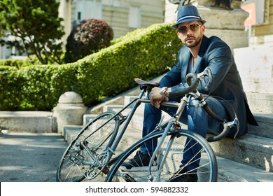 Stylish man in hat sitting on stairs on street with bicycle, waiting.
