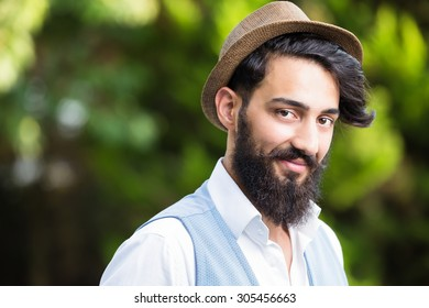 Stylish man head shot with hat and beard, green natural background.