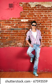 Stylish man in jeans and sunglasses leans red brick wall