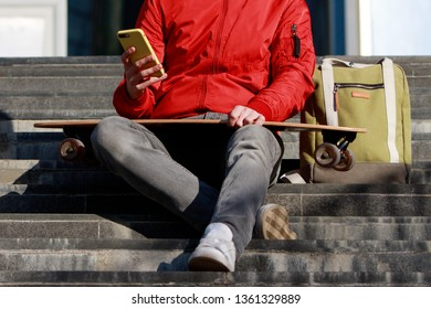 Stylish man longboarder in casual clothes using his smartphone, resting on the steps, sitting with longboard/skateboard outdoors, front view, cropped image. Urban, subculture, skateboarding concept