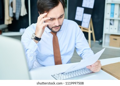Stylish man looking pensive while reading papers and creating new project while sitting at desk.