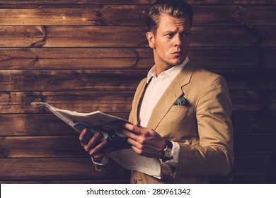 Stylish man with newspaper in rural cottage interior