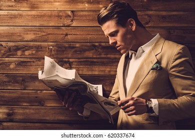Stylish man with newspaper in rural cottage interior.