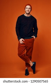 Stylish man in red trousers in a leopard color sweater and fashionable hats crossed his legs against an orange background