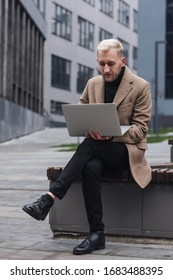 Stylish man sitting on the streets of the city near modern office centre and working with his laptop.