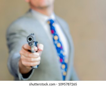 Stylish man in sports and polka dot tie points a gun