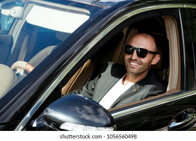 Stylish man in suit in black car. Business Man in glasses sitting in luxury auto. Success people. Millionaire gangster businessman boss