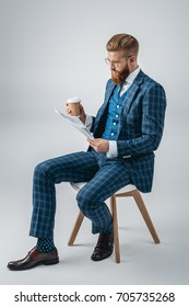 stylish man in suit with coffee to go reading newspaper while sitting on chair isolated on grey