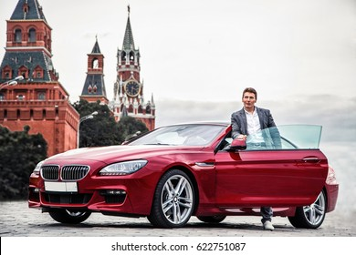 Stylish man in a suit standing near his expensive car with kremlin towers on bvackground