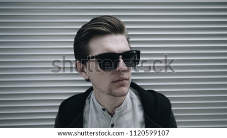 37635b615a7 Stylish man. Sunglasses. City style. A beautiful and charming man with  sunglasses outdoors