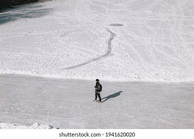Stylish man, tourist walks through the fresh snow and slippery ice in black clothes in winter, wandering around the countries. Photography, copy space.
