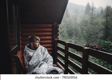 stylish man traveler in blanket relaxing on porch of wooden cabin in rainy day on background of woods in mountains. stylish hipster resting. space for text. atmospheric moment