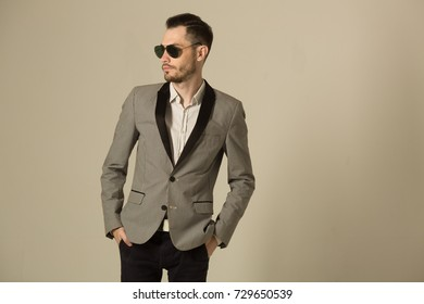stylish man with an unshaven face with a pensive face, in a suit on a light background in black glasses