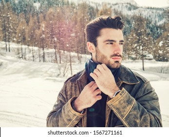 Stylish man walking confidently looking away on territory of contemporary winter resort covered in snow in the mountain