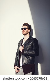 Stylish man wearing a black leather jacket leaning back against a wall on a sunny summer day
