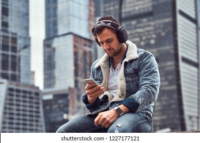 Stylish man wearing denim jacket listening to music and using smartphone sitting in front of skyscrapers in Moskow city at cloudy morning.