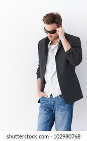 Stylish man wearing sunglasses, standing over white background.