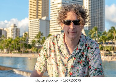 A stylish man wears shades and a Hawaiian shirt while visiting Waikiki Beach in Honolulu, Hawaii, with the beach and skyline beyond.