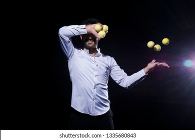 Stylish Man in white shirt posing for the camera. Man juggling yellow balls on black background.