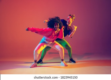 Stylish man and woman dancing hip-hop in bright clothes on green background at dance hall in neon light. Youth culture, hip-hop, movement, style and fashion, action. Fashionable portrait. - Shutterstock ID 1823945150