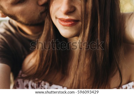 stylish man and woman hugging, kissing and smiling. tender romantic moment in summer evening light. sensual couple embracing. relaxing outdoors. true perfect feelings