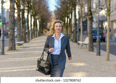 Stylish mature blond professional woman walking with her handbag down a city street on a tree lined walkway