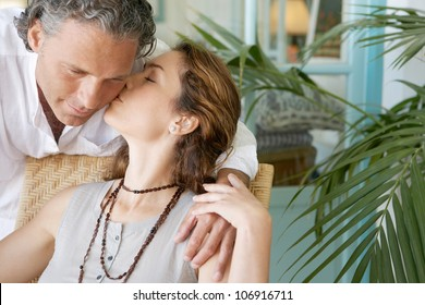 Stylish mature couple kissing at home.