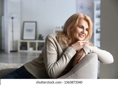 Stylish mature woman sitting in armchair at home