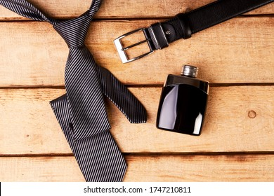 Stylish men accessories, men's fashion. Happy Father's Day concept with necktie, perfume bottle, leather belt and sunglasses