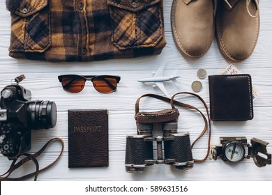 Stylish men set to travel, money, passport, airplane, hat, shoes, shirt, binoculars, sunglasses, camera, map, on vintage wooden background.