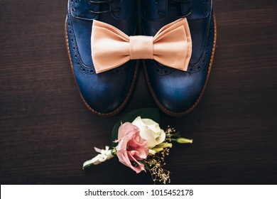 Stylish men's shoes on a dark wooden table next to the shoes is a pink butterfly, a boutonniere with live roses and a mechanical clock, the groom is ready for the wedding