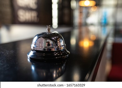Stylish metal bell for calling a bartender or waiter on the bar counter. Bell restaurant on the bar with bokeh