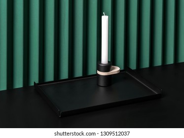 Stylish metal black support with same color candlestick with a wooden part and a white candle on the dark surface on the folded green wall background indoors. Closeup horizontal photo.
