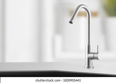 Stilvoller Metallkran in der Küche.Shiny-Wasserhahn in der Küche.Metallkran in Nahaufnahme.Moderne Möbel. Silberbecken als Küchenausstattung. Makrofoto von hoher Qualität. Metallischer Wasserhahn.