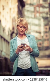 Stylish mid-age woman texting on the street