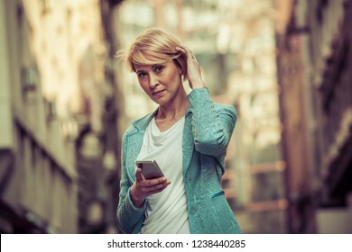 Stylish mid-age woman waiting for someone on the street