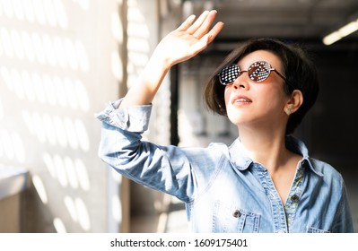 Stylish, middle aged Asian woman wearing 100% UV light protection sunglasses, stand inside and raise her hand to block out bright glare and sunlight from outside to avoid ultraviolet rays overexposure