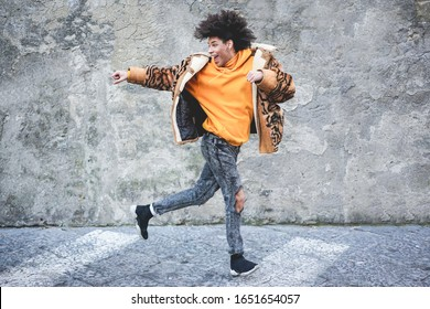 Stylish millennial guy dancing around city street outdoor - Young man having fun outside wearing trendy clothes - Z generation and fashion concept - Focus on his face