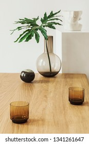 Stylish and minimalistic interior with tropical leaf in vase, woooden table, candles and stand with sculpture head. Modern room with design accessories. Eclectic home decor.