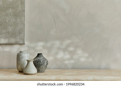 Stylish minimalistic monochromatic composition with design vases and personal accessories. Poster on the wall, copy space. Neutral colors. Template.