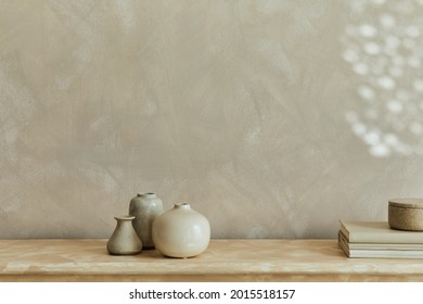 Stylish minimalistic monochromatic composition with design vases and personal accessories. Copy space. Neutral colors. Template.