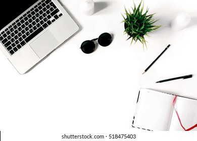Stylish minimalistic workplace with laptop keyboard, notebook, sunglasses and office plant in flat lay style. White background. Top view.