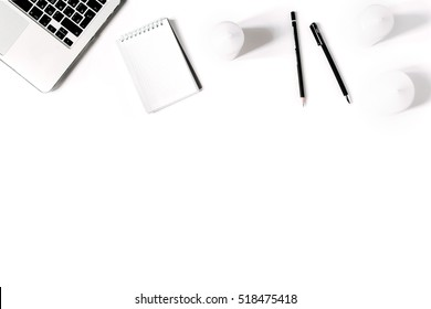 Stylish minimalistic workplace with laptop keyboard and notebook in flat lay style. White background. Top view.