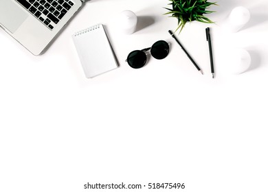 Stylish minimalistic workplace with laptop keyboard and notebook and sunglasses in flat lay style. White background. Top view.