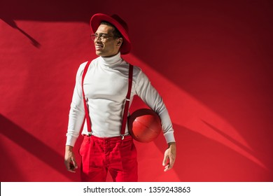 d4fbc46969a stylish mixed race man in hat and suspenders posing with basketball on red  with copy space