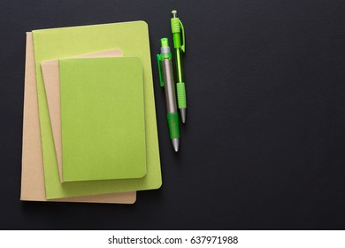 Stylish mockup with set of green notebooks on creative multicolored work space background, copy space, flat lay, concept of start-up and stationery supplies