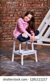cebe36bfc93d6 Stylish model child. Portrait girl kid teenager pose sitting on chair.  Beautiful brunette advertises