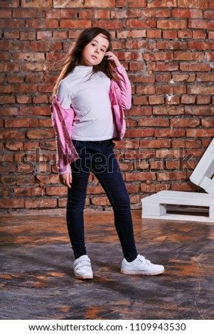 1f197f10b0235 Stylish model child posing background brick wall,loft interior. Fashion girl  kid hipster in casual clothes,pink jacket, white sneakers, jeans.