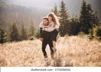 Stylish model couple in the autumn mountains. A young guy and a girl run along the slope against the background of the forest and mountain peaks at sunset.